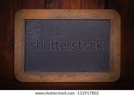 Blank chalkboard on wooden background - stock photo