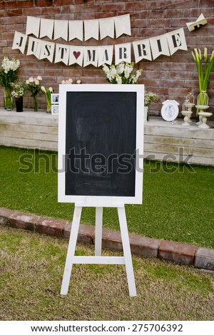 blank chalkboard sign with white frame and white stand in front of wedding ceremony. Wedding Decoration - stock photo