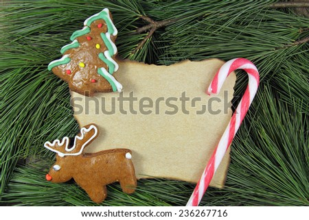 blank christmas card on fir tree with homemade gingerbreads - stock photo