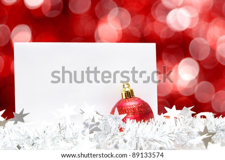 Blank Christmas greeting card with bauble, garland and abstract red light background - stock photo