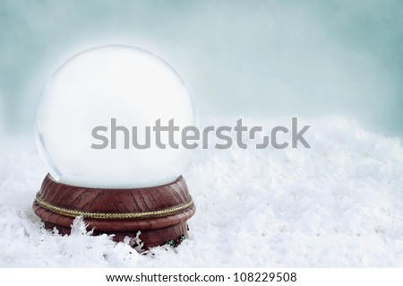 Blank Christmas snow globe with with copy space available against a blue background. Shallow depth of field with selective focus on snowglobe.