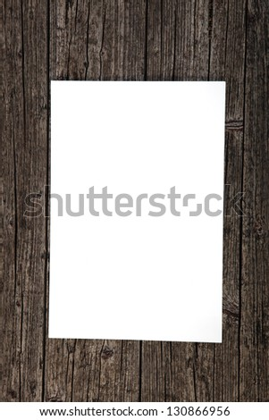 Blank clean white sheet of paper on a weathered stained textured wood background with copy space for your text - stock photo