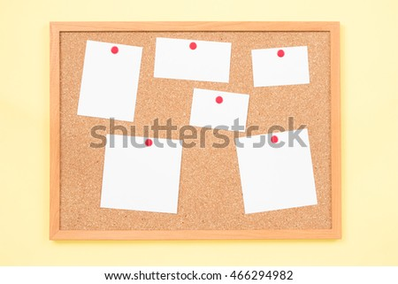 Blank color post it notes on a cork notice board on wood background.
