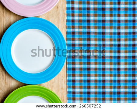 Blank colorful plates on wooden table and checked tablecloth background - stock photo