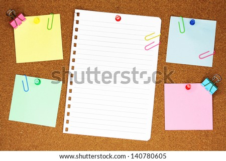 Blank, colourful notes pinned into brown corkboard with paper clips.