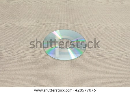 Blank Compact disc CD or DVD on brown fabric. - stock photo