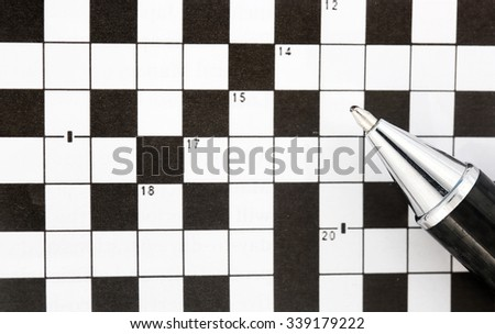 Blank crossword puzzle with a pen lying on top - stock photo