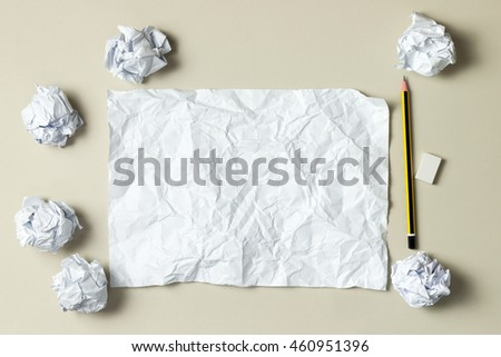 Blank crumpled paper on desk with pencil and paper balls - stock photo