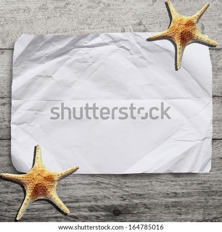 blank crumpled paper on wooden background with starfish.Vacation time! - stock photo