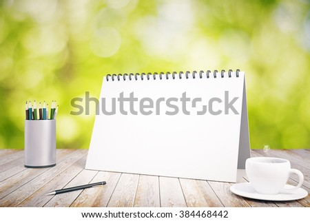 Blank diary cover on wooden table with pencils and cup of coffee, mock up - stock photo