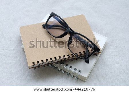 Blank diary, pen, and glasses on white background  - stock photo