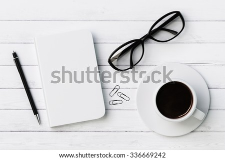 Blank diary, pen, cup of coffee, clips and glasses on white wooden table, mock up - stock photo