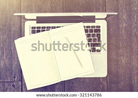 Blank diary with pencil with laptop on a wooden table - stock photo