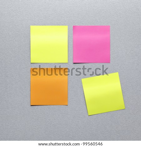 Blank different colors sticky note paper. On gray textured paper background. Closeup. - stock photo
