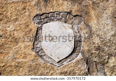 Blank emblem shield hewn in stone - stock photo