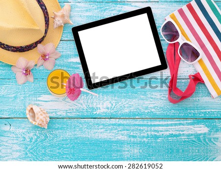Blank empty tablet computer on beach. Trendy summer accessories on wooden background pool. Sunglasses, orange juice and flip-flops on beach. Tropical flower orchid. Flat mock up for design. - stock photo