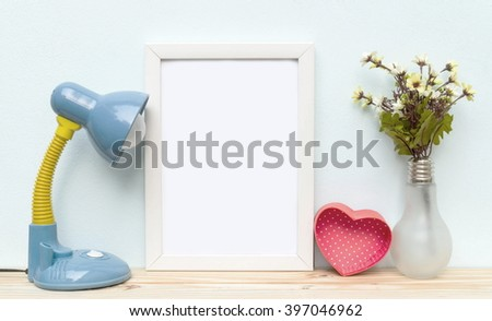 Blank frame, flower and heart on the table, mock up