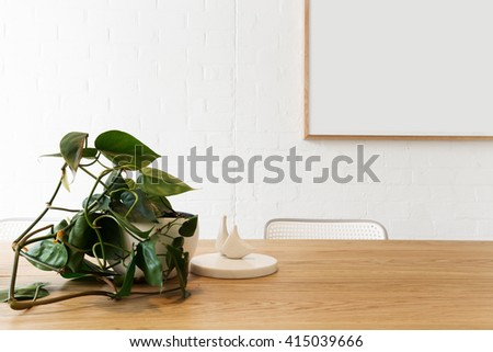 Blank framed artwork on white wall with scandi styled interior objects on wooden table - stock photo