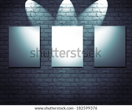 Blank frames on stone wall illuminated spotlights