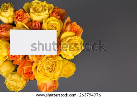 blank gift card and beautiful bouquet of orange and yellow roses over grey background - stock photo