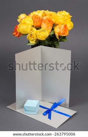 blank gift card, bouquet of orange and yellow rose flowers and gift box over grey background - stock photo