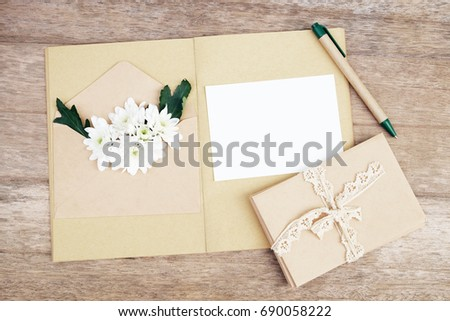blank gift card with white flower and brown envelop on wooden table.flat lay,top view