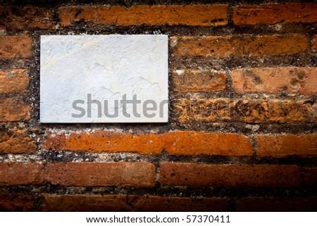 blank gray board on a brick wall - stock photo