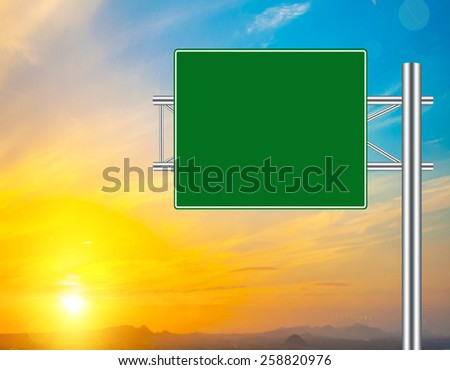 Blank Green Road Sign concept with resplendent clouds and sky. - stock photo