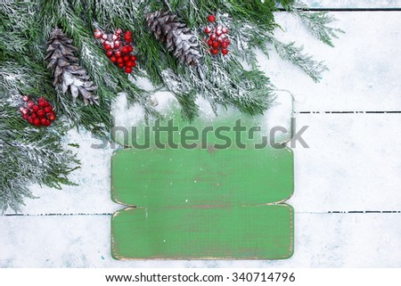 Blank green rustic sign with Christmas tree garland border on antique teal blue snowy wood background