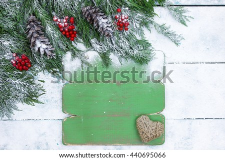 Blank green sign with tree branch, pine cones and red berries border on teal blue snow covered wooden background