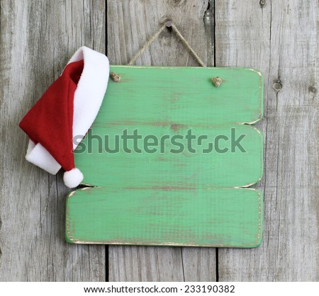 Blank green wood sign with Christmas Santa Claus hat hanging on antique rustic wooden background - stock photo