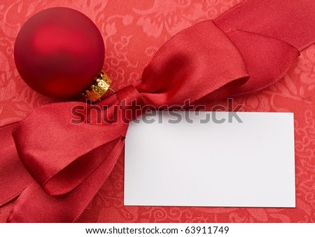 Blank greeting card or gift card decorated with red row and Christmas bauble. - stock photo