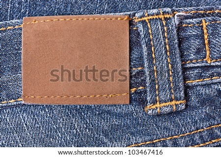Blank grunge leather label sewed on a blue jeans.