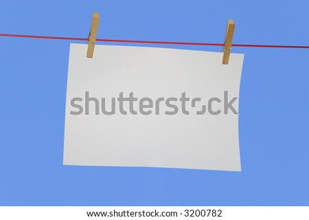 Blank horizontal paper on a washing line against a blue sky.