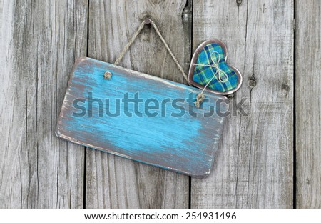 Blank ice teal blue wood sign with country heart hanging on rustic wooden background - stock photo