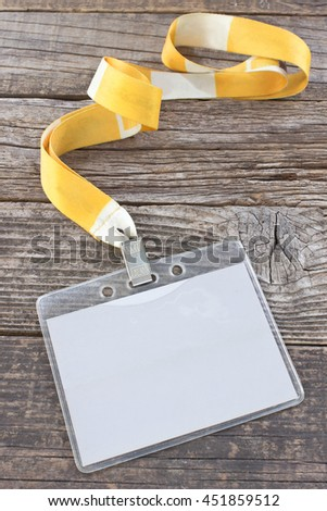 Blank ID card tag and yellow ribbon on wooden background - stock photo