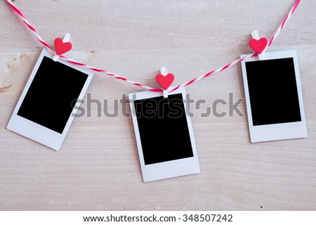 Blank instant photo and red clip paper heart hanging on the clothesline with wood background.Designer concept. - stock photo