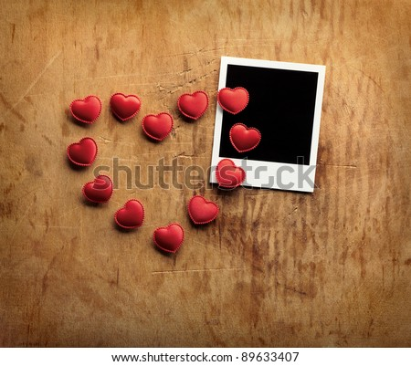 Blank instant photo and small red hearts lying in the shape of a heart on old dark grunge background. - stock photo
