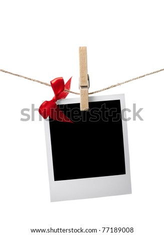 Blank instant photo and small red satin bow hanging on the clothesline. Isolated on white. - stock photo