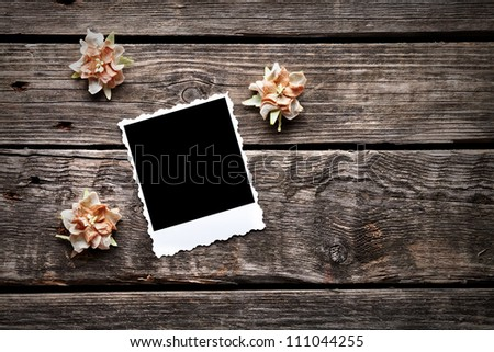 Blank instant photo frame with dried flowers on old wooden background.