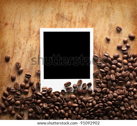 Blank instant photo with coffee beans on old dark grunge background. - stock photo