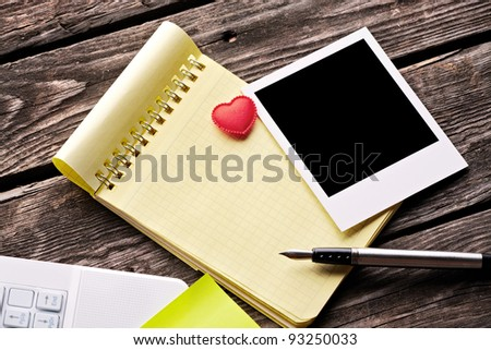 Blank instant photo with small red heart and ring binder on old wooden table. - stock photo