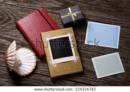 Blank instant photos, shell, present and notebooks - stock photo