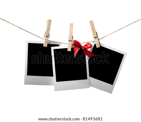 Blank instant photos with red bow hanging on the clothesline. Isolated on white. - stock photo