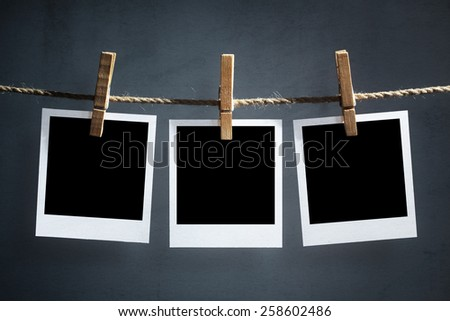 Blank instant print transfer photographs hanging on a clothesline - stock photo