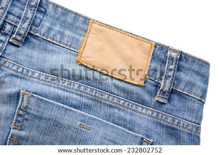 Blank leather jeans label sewed on a blue jeans. on white background. - stock photo