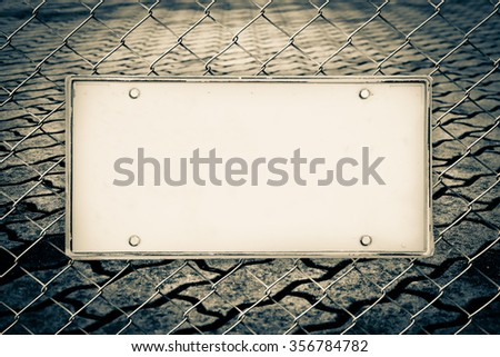 blank license plate on net fence and blur image of perspective old brick floor background - stock photo