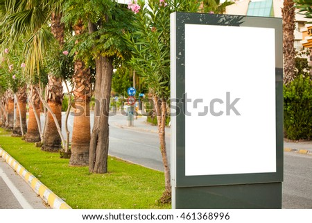 Blank lightbox on the city streets. Vertical.On the background of palm trees and greenery
