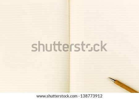 Blank lined notebook with pen placed at a diagonal. - stock photo