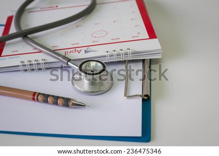 Blank medical clipboard with stethoscope and calendar - stock photo